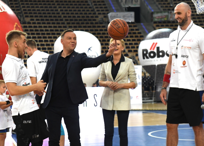 Andrzej Duda (second left) tries his hand at basketball, watched by  Marcin Gortat (right). Photo: PAP/Grzegorz Michałowski