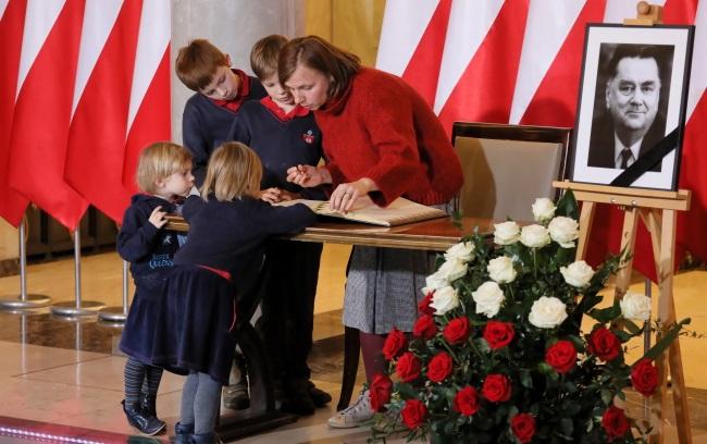 Жители Варшавы оставляют свои записи в книге соболезнований в связи со смерью Яна Ольшевского, которая выставлена в Канцелярии премьер-министра