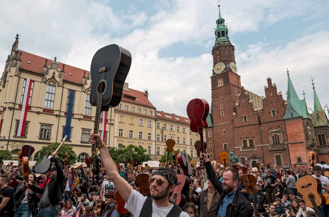 Guitar players gather in Wrocław's market square.