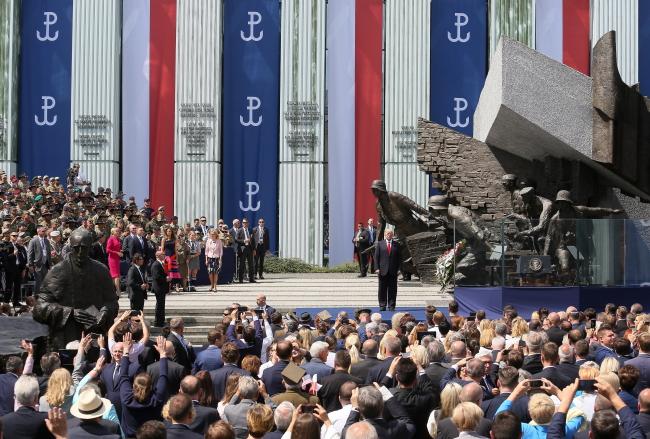 Поляки слушают выступление президента США Дональда Трампа у памятника Варшавскому восстанию на площади Красиньских в Варшаве.