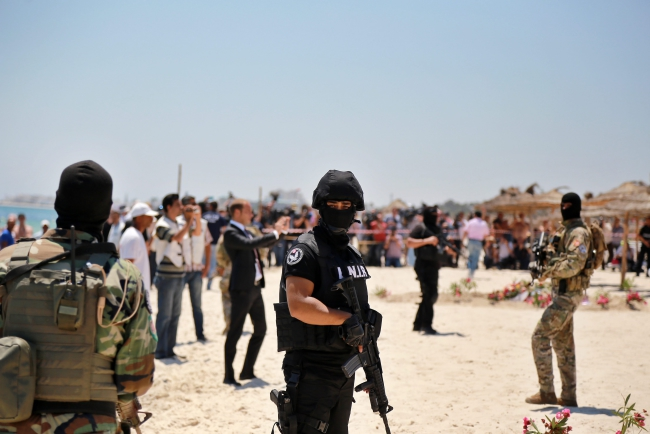 Members of the Tunisian Security Services stand guard during a wreath laying ceremony at the site of a terror attack on tourists on a beach outside the Imperial Marhaba Hotel, al-Sousse, 140km east of Tunis, Tunisia. Photo: EPA/Stringer