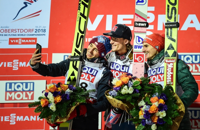 From left to right: silver medal winner Kamil Stoch of Poland, gold medal winner Daniel Andre Tande of Norway and bronze medal winner Richard Freitag take a selfie after the Ski Flying World Championships in Oberstdorf, Germany, 20 January 2018. Photo: EPA/Philipp Guelland