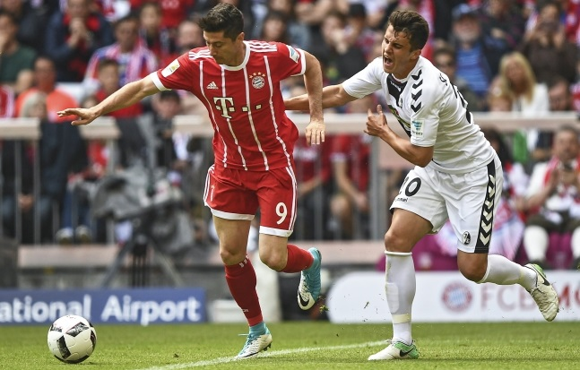 Robert Lewandowski (left) of Bayern Munich in action against Marc-Oliver Kempf of SC Freiburg. Photo: EPA/CHRISTIAN BRUNA