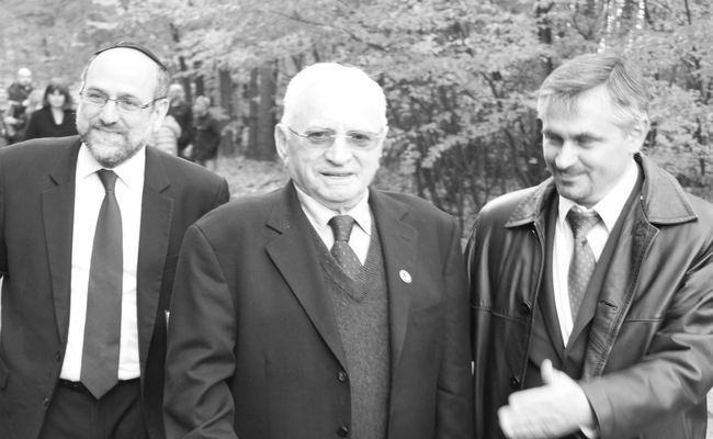 Tomasz Blatt (C) on the terrain of the former Nazi German death camp if Sobibór in 2013, with Chief Rabbi of Poland Michael Schudrich (R). Photo: wikimedia commons/Anton Kurt
