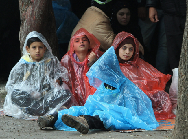 Migrants children from Syria shelter from the rain in front of the registration camp in the town of Presevo, South Serbia, 20 October 2015. About 6,000 migrants entered into Serbia from Macedonia during the last 24 hours said in the Serbian Commissariat for Refugees. Photo: EPA/DJORDJE SAVIC