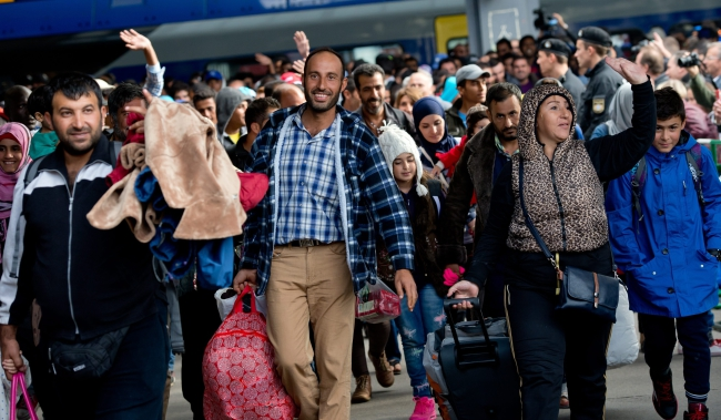 Refugees cheer as they arrive at the main train station in Munich, Germany, 06 September 2015. Many of the refugees are fleeing war-torn countries such as Syria and Afghanistan, and thus qualify for international protection, but EU countries disagree on how to best handle the surge. EPA/SVEN HOPPE