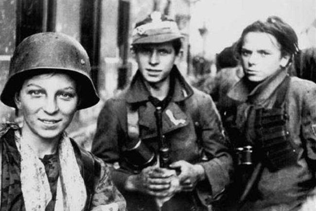 """Polish scouts fighting in the 1944 Warsaw Uprising. Source: Anna Świrszczyńska """"Swir"""" (1984), Budowałam Barykadę, Kraków: Wydawnictwo Literackie. Photo: Jerzy Tomaszewski [Public domain], via Wikimedia Commons."""