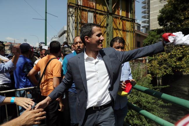 Председатель Национальной ассамблеи Венесуэлы Хуан Гуайдо (в центре) прибыл, чтобы выступить с речью во время марша против правительства Николаса Мадуро в Каракасе