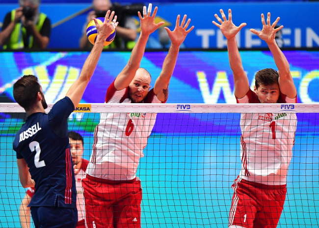 Aaron Russell (L) of the USA in action against Polish players Bartosz Kurek (C) and Piotr Nowakowski (R) during the FIVB Volleyball Men's World Championship semi final match between Poland and the USA in Turin, Italy, 29 September 2018. Photo: EPA/DANIEL DAL ZENNARO