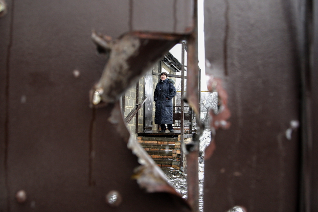 A local woman is seen through a shell hole in a fence of a damaged home after shelling in Donetsk, Ukraine, 09.02.2015. The leaders of Germany, France, Ukraine and Russia plan to hold an emergency summit on the Ukrainian conflict in Minsk on 11 February, with the meeting being described as a last-ditch attempt to find a peaceful solution to the cri