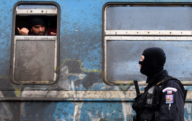 A Czech police officer assisting his Macedonian colleagues in patrolling and organizing the transport of refugees with trains to Serbia, speaks with a migrant in a train at a station near the town of Gevgelija, The Former Yugoslav Republic of Macedonia, 8 February. Photo: EPA/NAKE BATEV.