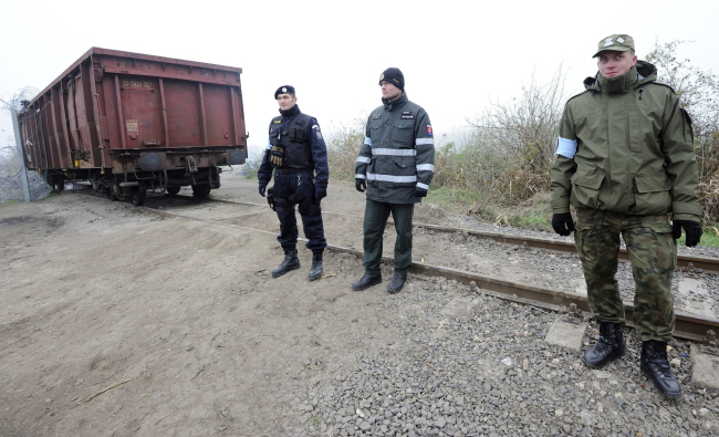A Czech and a Slovakian policeman along with a Polish border guard patrol the area at the train wagon to be used as the border closure between Hungary and Serbia on the Hungarian-Serbian border near Roszke, some 180 kilometers southeast of Budapest, Hungary, 07 November 2015. EPA/ZOLTAN GERGELY KELEME