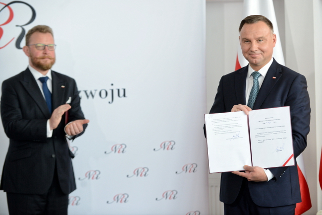 Poland's Health Minister Łukasz Szumowski (left) and President Andrzej Duda (right) during a ceremony of signing the national cancer strategy bill, in Warsaw on Monday