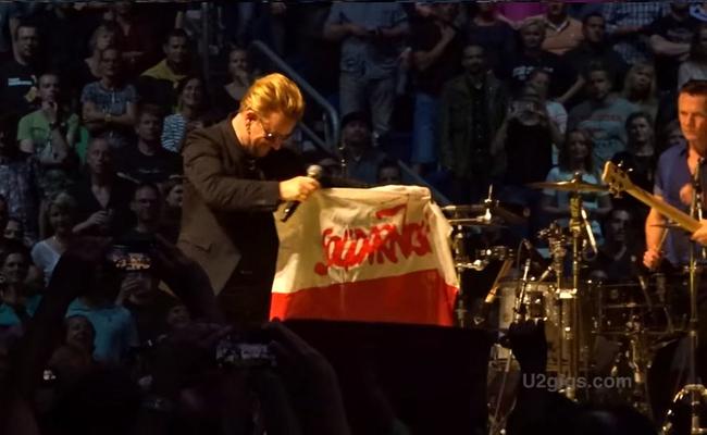 Bono brandishing a Polish flag in Berlin. Photo: youtube