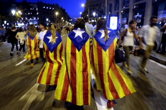 Catalan people wear pro-independence regional flags in Barcelona, northeastern Spain. Photo: EPA/ALBERTO ESTEVEZ