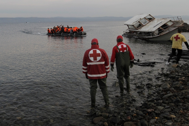 Refugees and migrants arrive in an overloaded rubber dinghy on the Greek island of Lesbos (Lesvos) as Red Cross staff wait to assist them, Greece, 16 November 2015 after crossing the Aegean Sea from Turkey. EPA/ORESTIS PANAGIOTOU