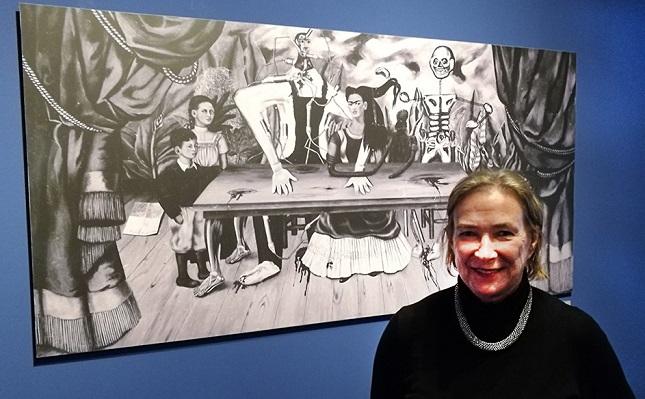 """Kuratorin Dr. Helga Prignitz-Poda. Im Hintergrund eine Reproduktion des verschollenen Gemäldes """"Der verletzte Tisch""""."""