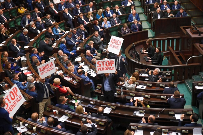 Opposition MPs hold placards demanding a state inquiry into pedophilia allegations against priests as the lower house of Poland's parliament debates tougher penalties for child sex abuse on Thursday evening. Photo: PAP/Radek Pietruszka