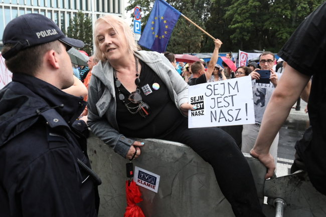 """A protester shows a police officer a sign which reads: """"The parliament is ours"""". Photo: PAP/Tomasz Gzell."""
