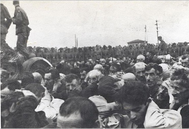 Jewish men, with hands on heads, are watched over by Nazi guards as the ghetto in Białystok is liquidated in August 1943. Photo: Public Domain