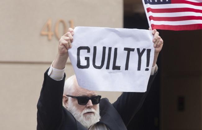 """Активист у здания суда. Надпись на плакате: """"Виновен"""""""