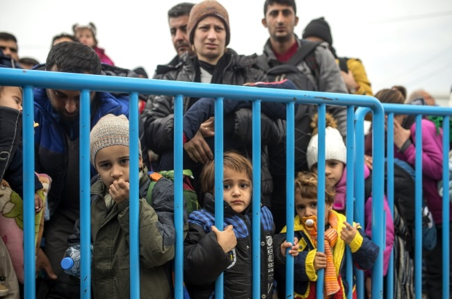 Refugees and migrants wait for permission to leave the registration and transit camp to board a train headed for Serbia, near the city of Gevgelija, the Former Yugoslav Republic of Macedonia. Photo: EPA/GEORGI LICOVSKI
