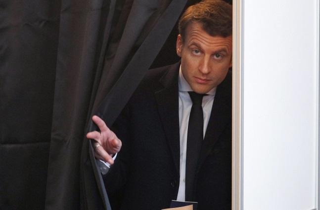 Emmanuel Macron steps out of a voting booth during the French presidential election. Photo:  EPA/CHRISTOPHE ENA / POOL