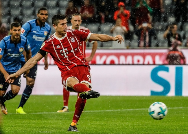 Lewandowski slots home the penalty to put Bayern 3-0 up against Leverkusen in Munich on Friday. Photo: EPA/RONALD WITTEK