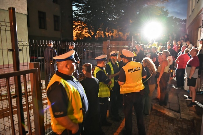 A throng gathers as investigators question the suspect at a prosecutor's office in the southwestern town of Świdnica on Sunday evening.
