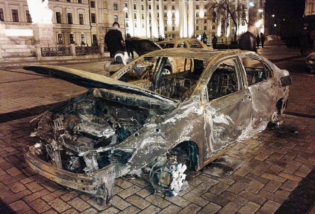 A charred civilian vehicle from Mariupol after the 2015 attack, on show in Kiev.  Photo: Qypchak/Wikimedia Commons (CC BY-SA 4.0)
