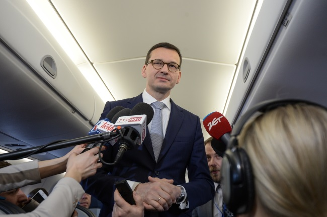 PM Mateusz Morawiecki takes questions from reporters on board a plane bound for Warsaw before leaving Brussels. Photo: PAP/Marcin Obara