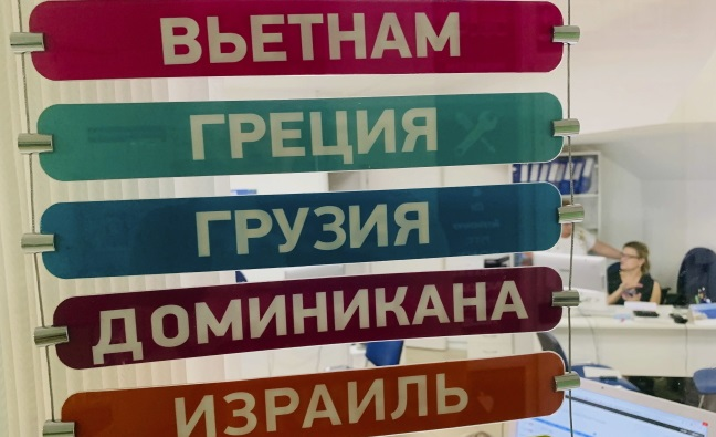 Работники турфирмы pа витриной с названиями возможных направлений в Москве