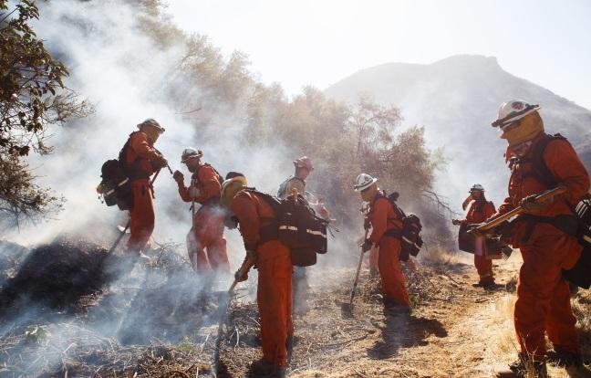 Пожарные работают над тушением пожара на склоне холма в Уэст-Хиллз, штат Калифорния, США