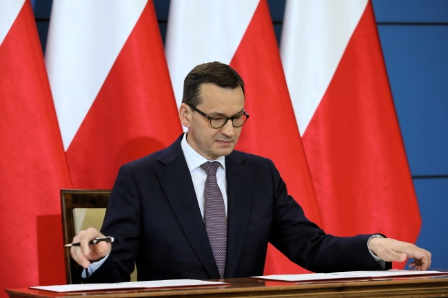 Polish Prime Minister Mateusz Morawiecki signs the joint Polish-Israeli declaration during a news conference in Warsaw on Wednesday. Photo: PAP/Leszek Szymański