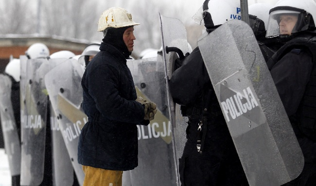 A miner from JSW stood before riot police during a confrontation at the company's HQ on Monday. Photo: PAP/Andrzej Grygiel
