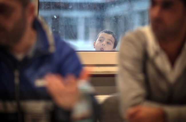 A boy looks inquisitively through a window while two refugees from Syria describe their experiences to Irene Alt (not pictured), integration minister of Rhineland-Palatinate, at the asylum seekers reception centre in Ingelheim, Germany, 17 November 2015. Photo: EPA/FREDrIK VON ERICHSEN
