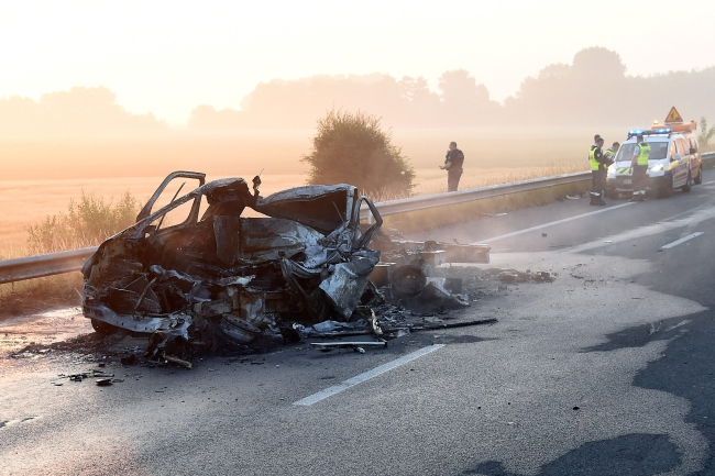 Rescue team and firefighters secure a perimeter near the wreckage of a burnt van following a crash on the A16 highway, near Calais, northern France. Photo: EPA/GUY DROLLET