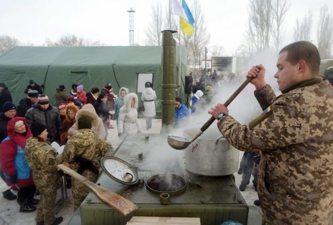 Ukrainian servicemen distribute hot food and tea to local citizens in the eastern city of Avdiivka, Donetsk area, Ukraine. Photo: PAP/EPA/Markiian Lyseiko.