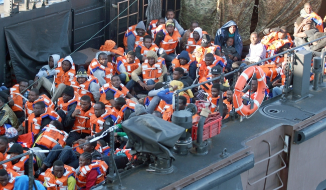 A handout image made available by the British Ministry of Defence (MOD) on 13 May 2015 of migrants arriving in the safety of HMS Bulwark's dock on a Landing Craft in the Mediterranean. Photo: PAP/EPA/CARL OSMOND/MOD/CROWN COPYRIGHT