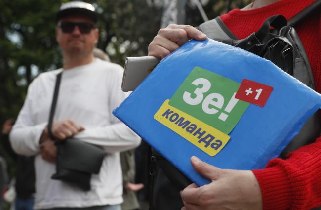 """Женщина держит папку с наклейкой """"Зе+1 команда"""", требуя установить дату инаугурации Володымыра Зеленского 19 мая 2019 года"""