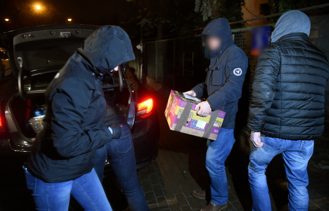 Plain-clothes police officers remove packages from the Warsaw house of late communist leader General Wojciech Jaruzelski. Photo: PAP/Radek Pietruszka
