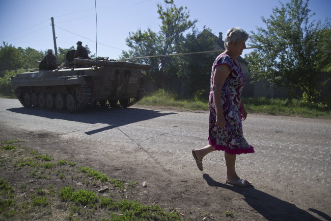 A woman passes Ukrainian servicemen as they ride on an armored military vehicle not far of Artemivsk city of Donetsk area, Ukraine, 09 June 2015. Photo: PAP/EPA/ALEX ROM