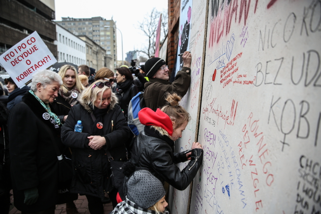"Protesters outside the Law and Justice (PiS) party building write messages on a ""wall of fury"" on International Women's Day. Photo: PAP/Rafał Guz."