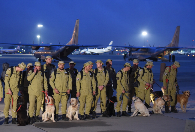 Members of the HUSAR heavy search and rescue team and their dogs at Warsaw's Okęcie Military Airport. Photo: PAP/Radek Pietruszka