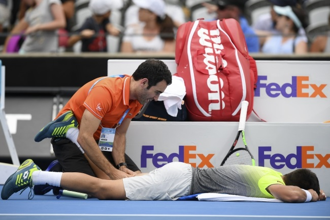 Damir Dzumhur of Bosnia and Herzegovina recieves attention from medical staff during a singles match against Alex de Minaur of Australia at the Sydney International Tennis Tournament in Sydney, Australia, on Wednesday. Photo: EPA/DAN HIMBRECHTS