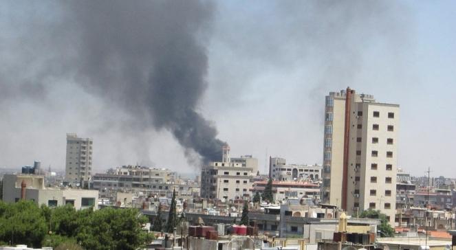 Dym nad miastem Homs w Syrii