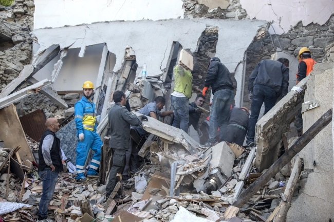Firefighters search for people in a collapsed house in Fonte del Campo near Accumoli, central Italy, after Wednesday's earthquake. Photo: EPA/ANGELO CARCONI