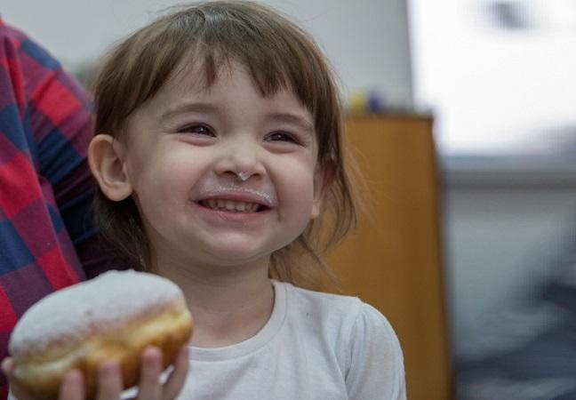 A little girl enjoys her pączek. Photo: PAP/Andrzej Grygiel.