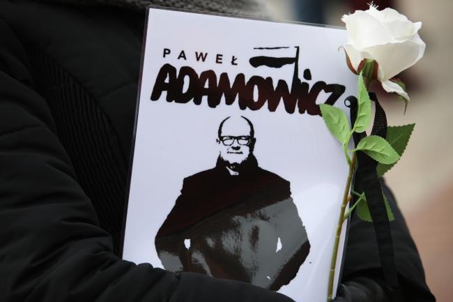 Одна из жительний Варшавы, пришедшая на Замковую площадь в Варшаве, чтобы посмотреть трансляцию похоронной церемонии убитого мэра Гданьска Павла Адамовича