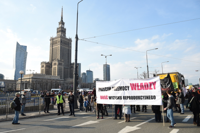 "Protesters carry a banner which reads ""Against authoritarian abuse. Enough reproductive exploitation"". Photo: PAP/Radek Pietruszka."